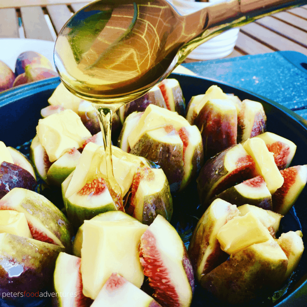 pouring honey over figs, ready for roasting