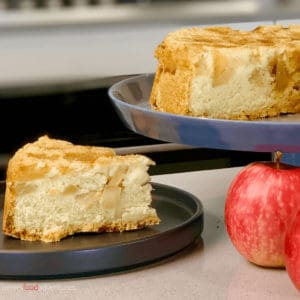 Piece of Russian Apple cake on a plate, beside a cake stand