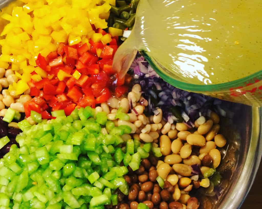 Pouring dressing over 7 Bean Salad