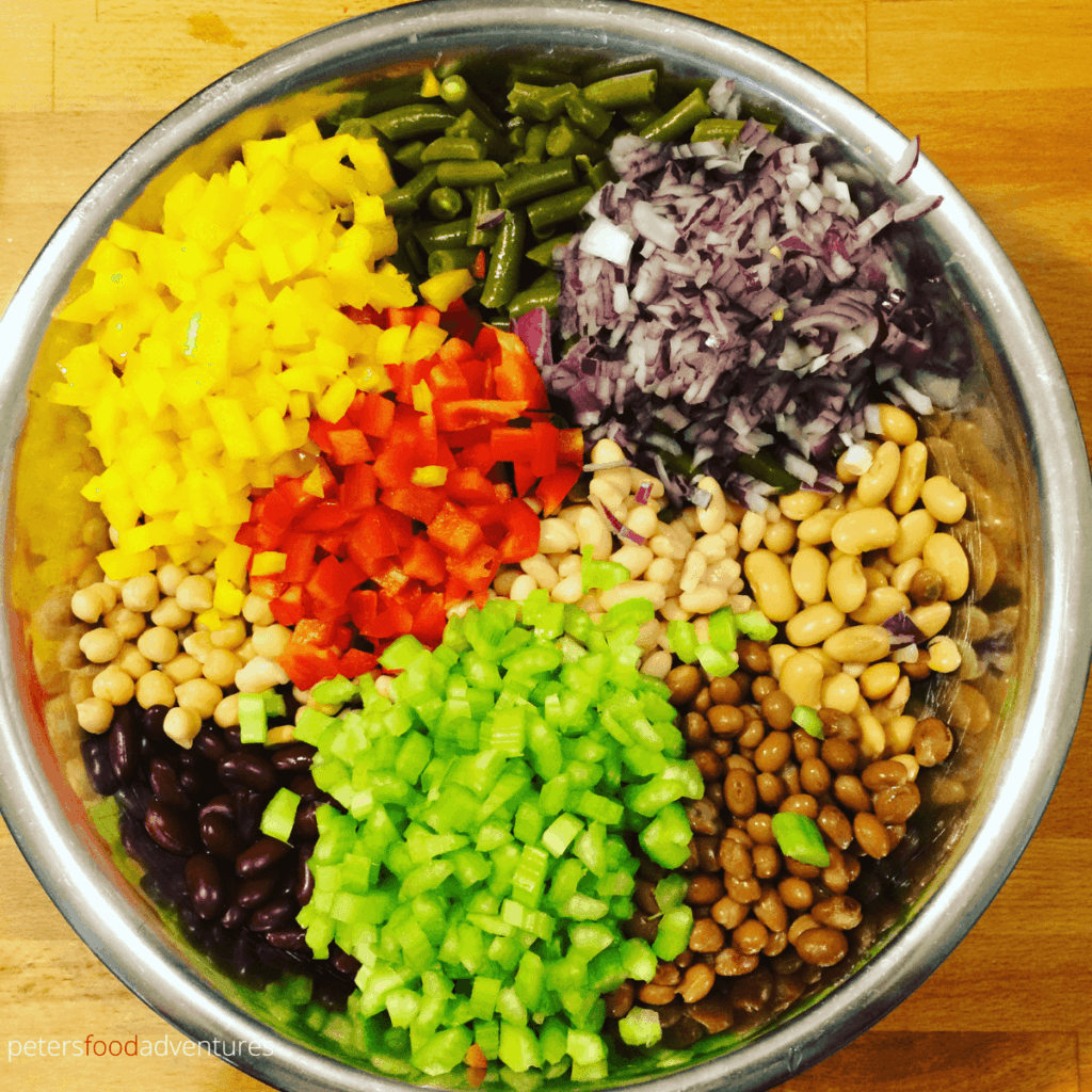making 7 bean salad with canned bean, celery, red peppers in a large bowl