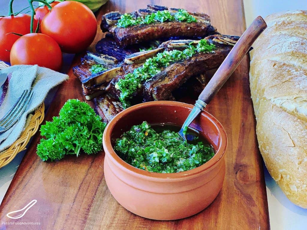 Chimichurri in a bowl, spread over Asado ribs on a table
