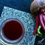 Russian Beet Kvass (Свекольный квас) in a glass beside fresh beets