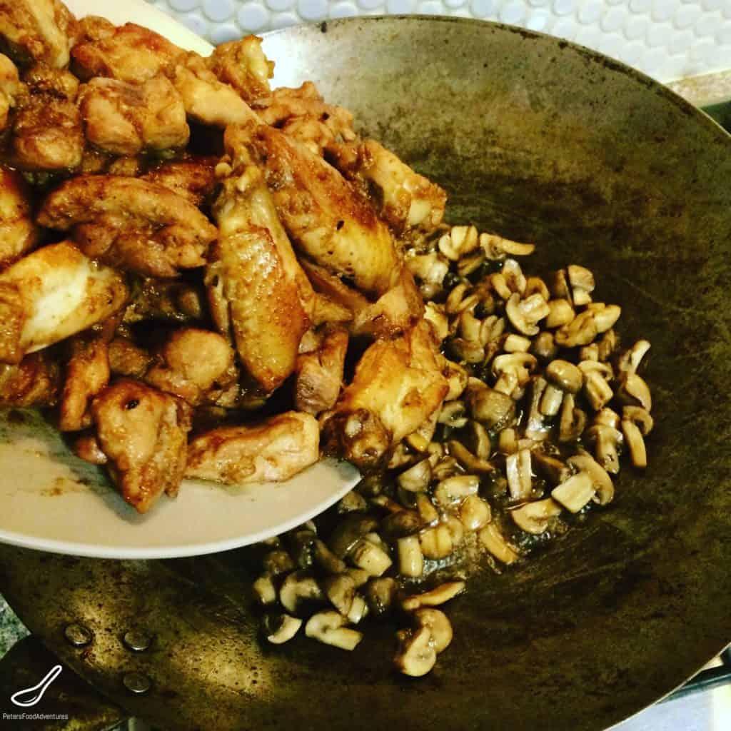 wok adding chicken wings