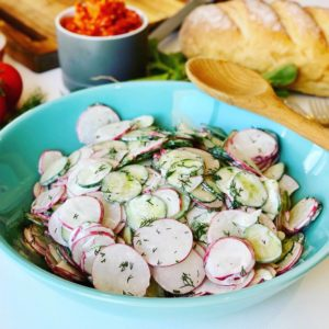 Radish and Cucumber Salad in a bowl on a kitchen table (Салат из редиски )