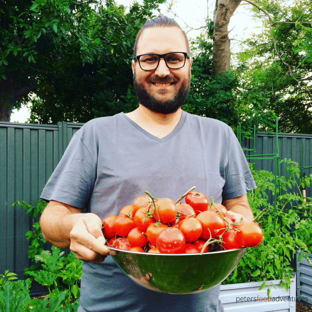 man holding a bowl of tomatoes picked from the garden