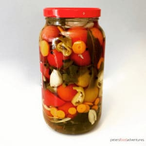 Enjoy your fresh, garden tomatoes by preserving them Russian-style. Pickled Tomatoes (солёные помидоры) with garlic and fresh herbs. I stuff extra vegetables between the tomatoes to make pickled vegetables too. These canned tomatoes are a staple year round.