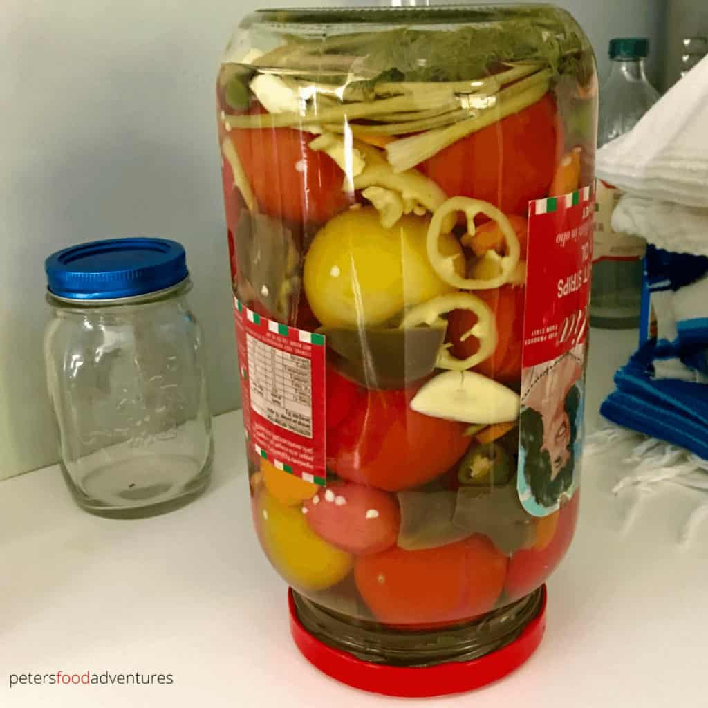 glass jar filled with pickled tomatoes and vegetables, upside down on a counter