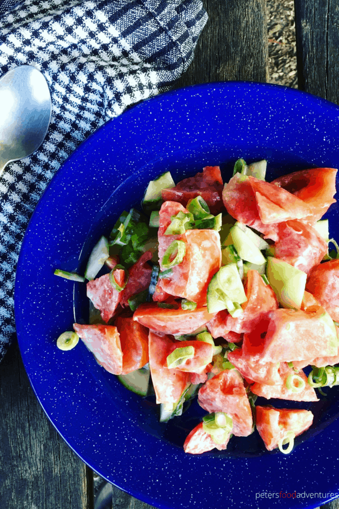 This Creamy Tomato Cucumber Salad is an easy rustic Russian salad, made with tomatoes, green onions, cucumbers, dill and whipping cream. A tasty addition to your summer salad dinner recipes.