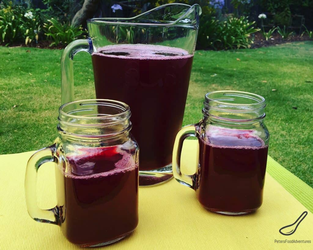 Glasses filled with fruit kompot beside a glass pitcher