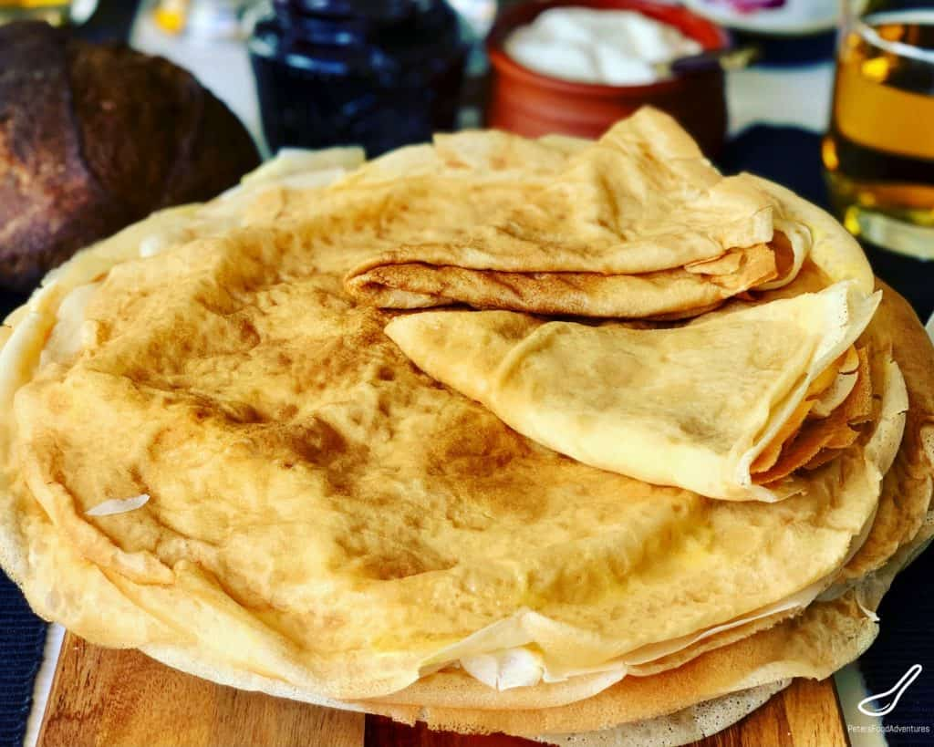 These Russian Pancakes commonly known as Blinchiki, Crepes, Blintzes or Blini are a staple food in Slavic countries. Often they are stuffed and rolled. I love eating them with butter, sour cream and blueberry jam. This is my lower fat blini recipe. Easy and delicious Russian Crepes or Blini Recipe (Блины)