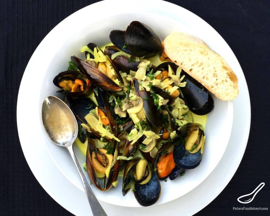 Steamed Mussels in White Wine in a bowl with a french bread
