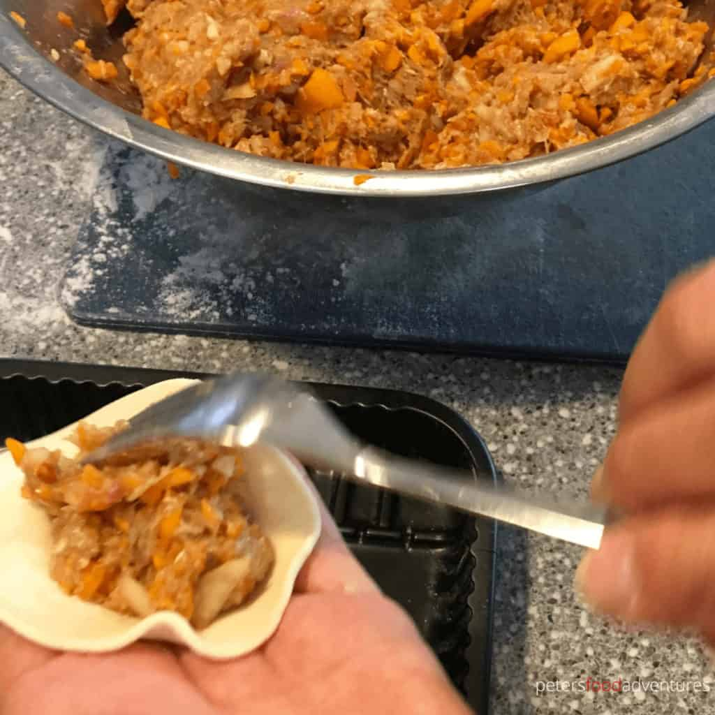 placing meat filling to manti