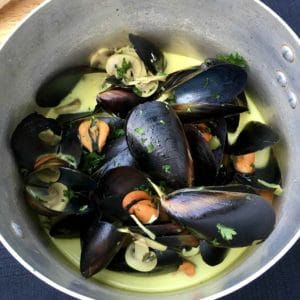 This delicious Steamed Mussels in a creamy white wine is easy to make and sure to impress with wine, cream, garlic and mushrooms. Mop up the sauce with a piece of bread. Perfect as an appetizer for as a dinner meal, this recipe is a keeper.