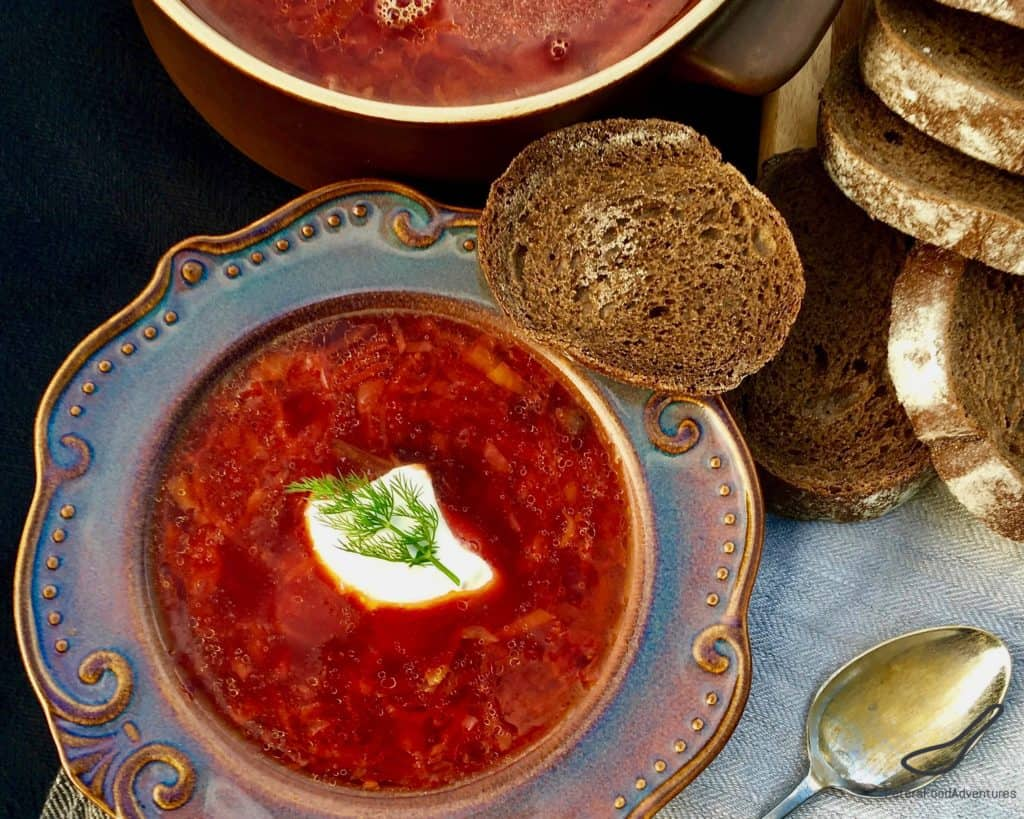 Top down view of a bowl of borscht with rye bread with a dollop of sour cream