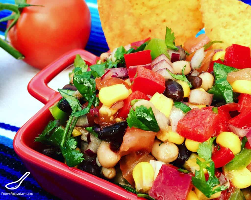 This Texas Caviar recipe is a Texan classic that's sure to be King of the Bbq this summer! Toss the ingredients together and you're done! It's like a supercharged bean salad, or a perfect to dip with Doritos- This recipe is a keeper! Cowboy Caviar Bean Salad and Dip