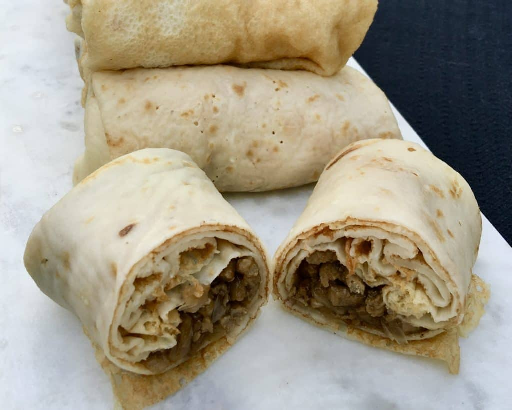 Russian Stuffed Blinchiki, also called Russian Crepes, are a thin rolled pancake stuffed full of savory meaty goodness. Not dry, fully of flavor and juicy. Meat Blini (Блинчики с мясом)