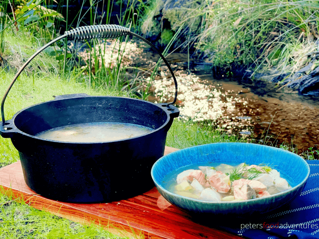 Rustic Russian Fish Head Soup, Ukha (Уха), in a bowl beside a cast iron pot it was cooked in, beside a creek