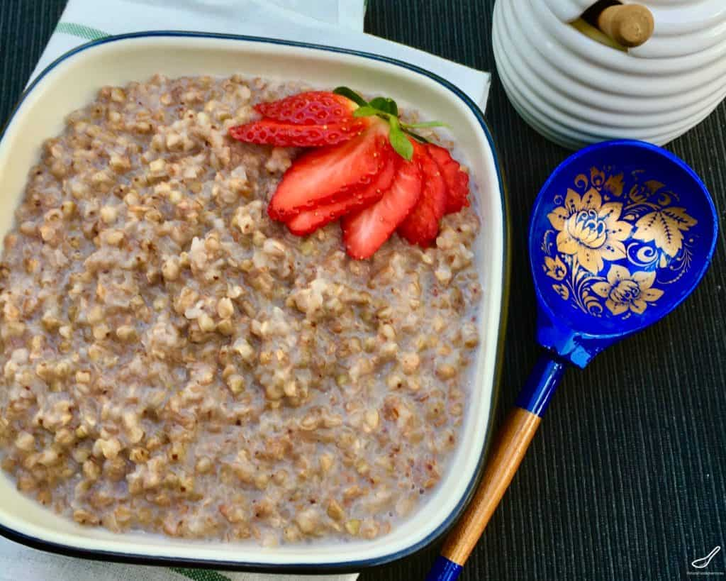 buckwheat porridge made with milk in a bowl with fresh strawberries