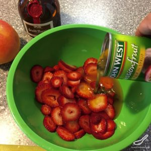 Canned Passionfruit pouring over sliced strawberries