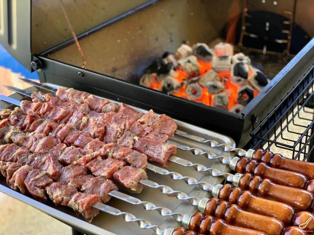 marinated lamb skewers beside hot charcoals mangal