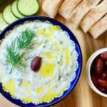 Tzatziki Sauce (meze) in a bowl served with olives, bread and cucumbers