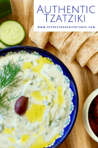 Authentic Tzatziki sauce in a bowl beside bread, olives and cucumbers