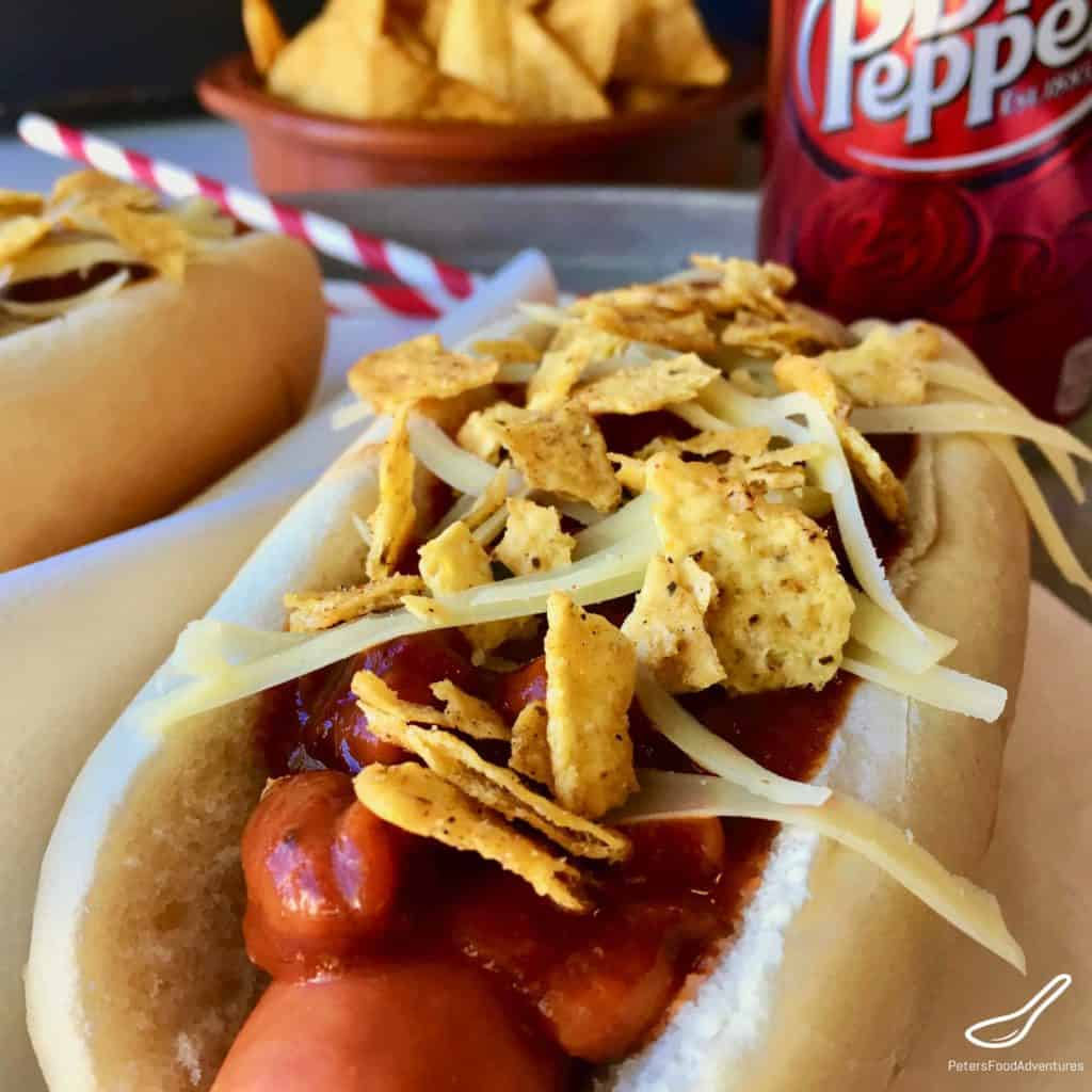 hot dog topped with chili, doritos, cheese and jalapeños