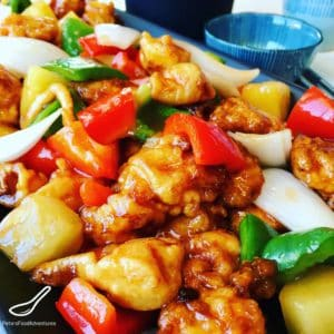 Boneless Sweet and Sour Pork in a crispy batter, food court style. The sauce is so easy to make with the sweetness of pineapple, bell peppers and onion. Tastes just like take out!