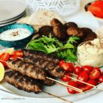 platter of lamb kofta kebabs with hummus, tzatziki, lettuce and plates