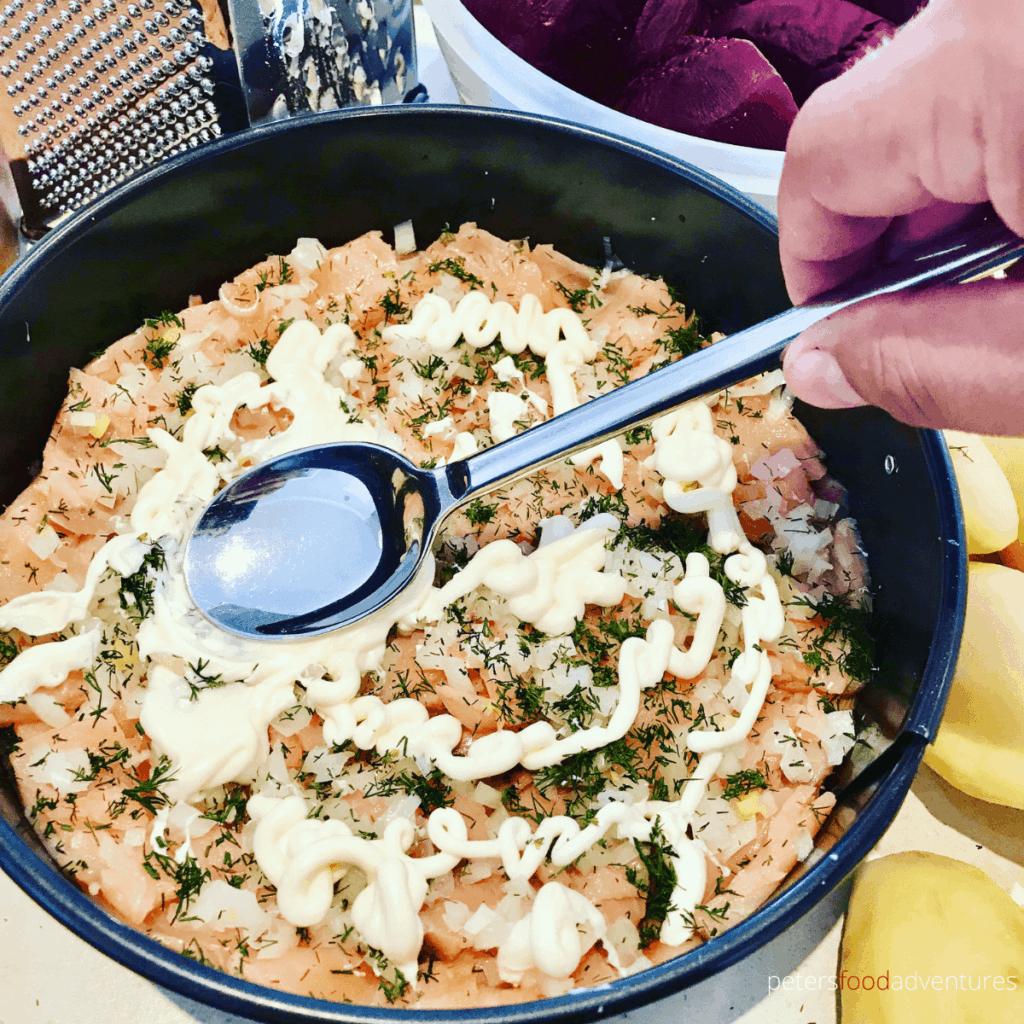 spreading mayo on a layer of shuba salad