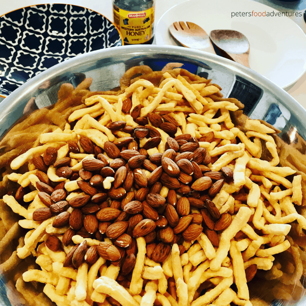 mixing chak chak with almonds in a bowl