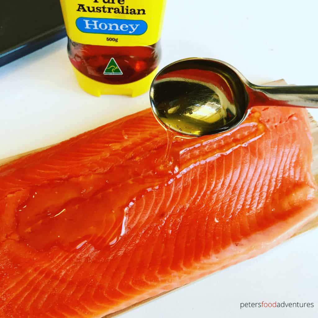 spooning honey over fresh trout fillet