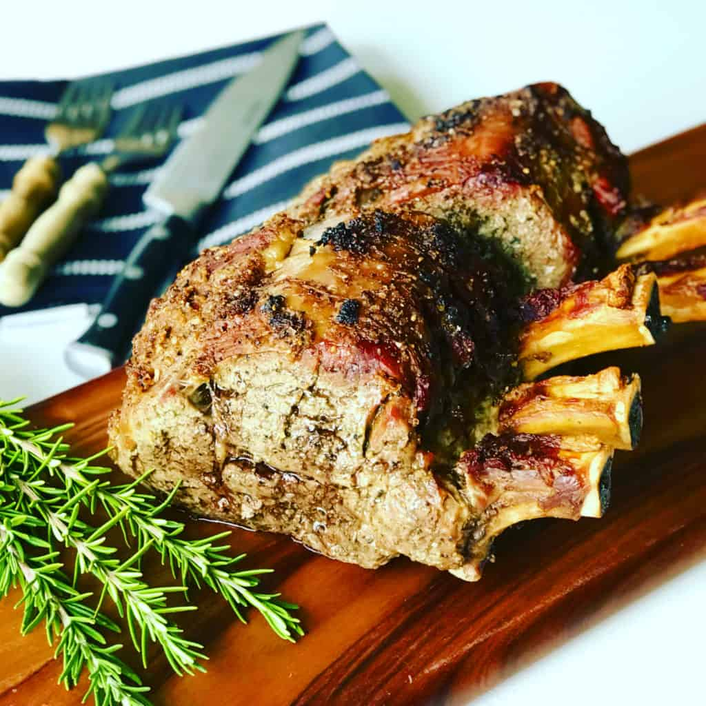 Prime Rib on a cutting board with fresh rosemary and carving set