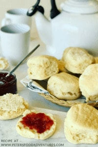 Scones in a basket on a breakfast table with tea cup and a kettle.