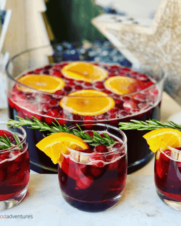 This Christmas Punch recipe with whole Cranberries is a tasty drink that's super easy to make, perfect for holiday parties. A non alcoholic cranberry party punch, the whole family can enjoy.