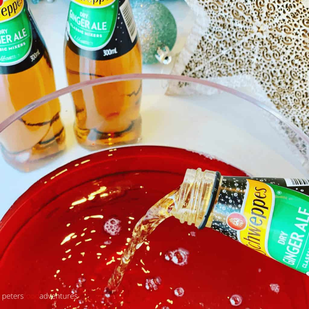 pouring ginger ale into cranberry punch