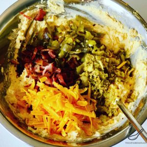 Egg yolks, cheese, bacon and jalapenos in a mixing bowl
