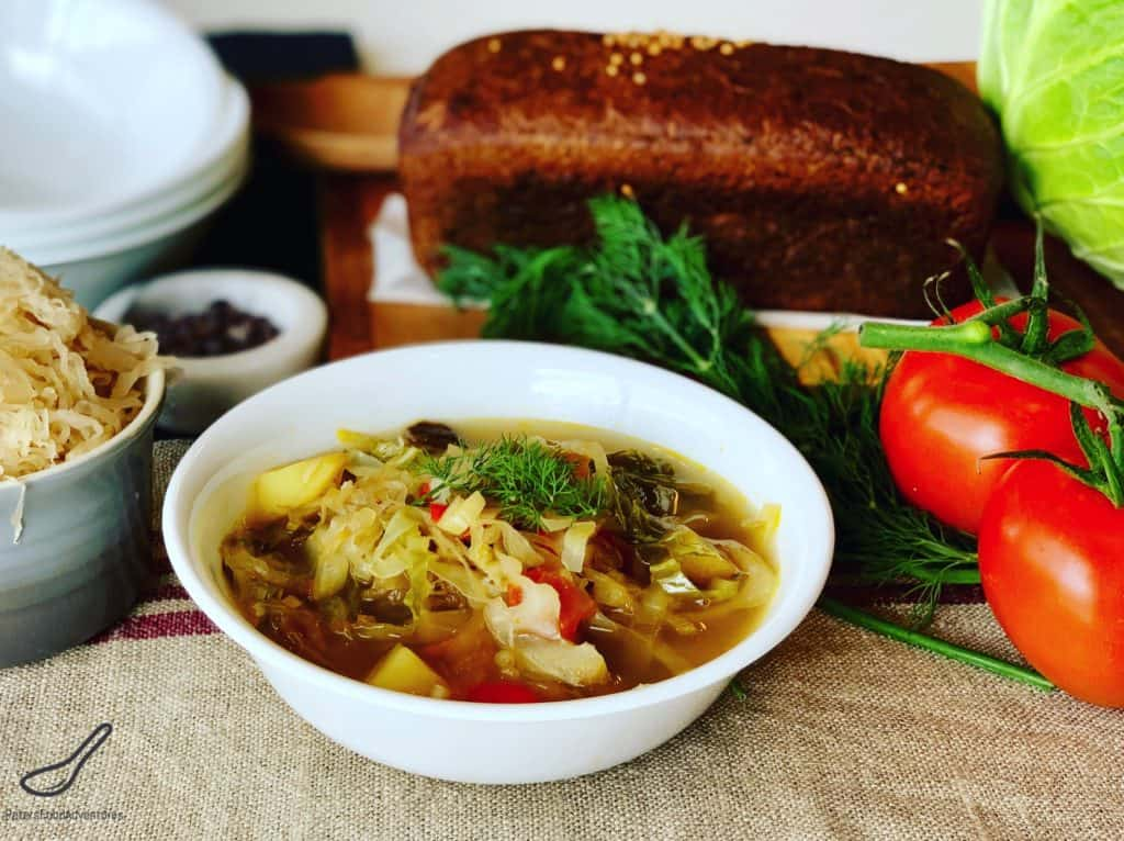 Cabbage Soup served in a bowl with rye bread on a table