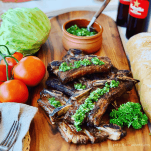 Argentine Bbq Beef Ribs - Asado style is a tasty way to enjoy your short cut ribs this summer. Flanken-style short ribs, cut cross the bone and bbq'd to perfection. Served with homemade Chimichurri sauce.