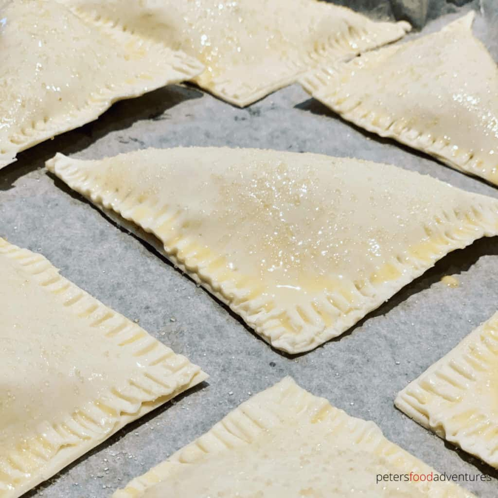 unbaked apple turnovers on a baking tray