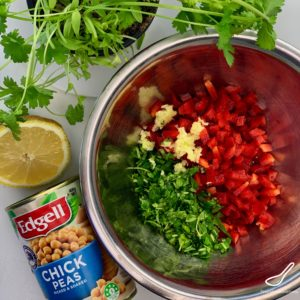 Garbanzo beans in a bowl with red peppers and cilantro