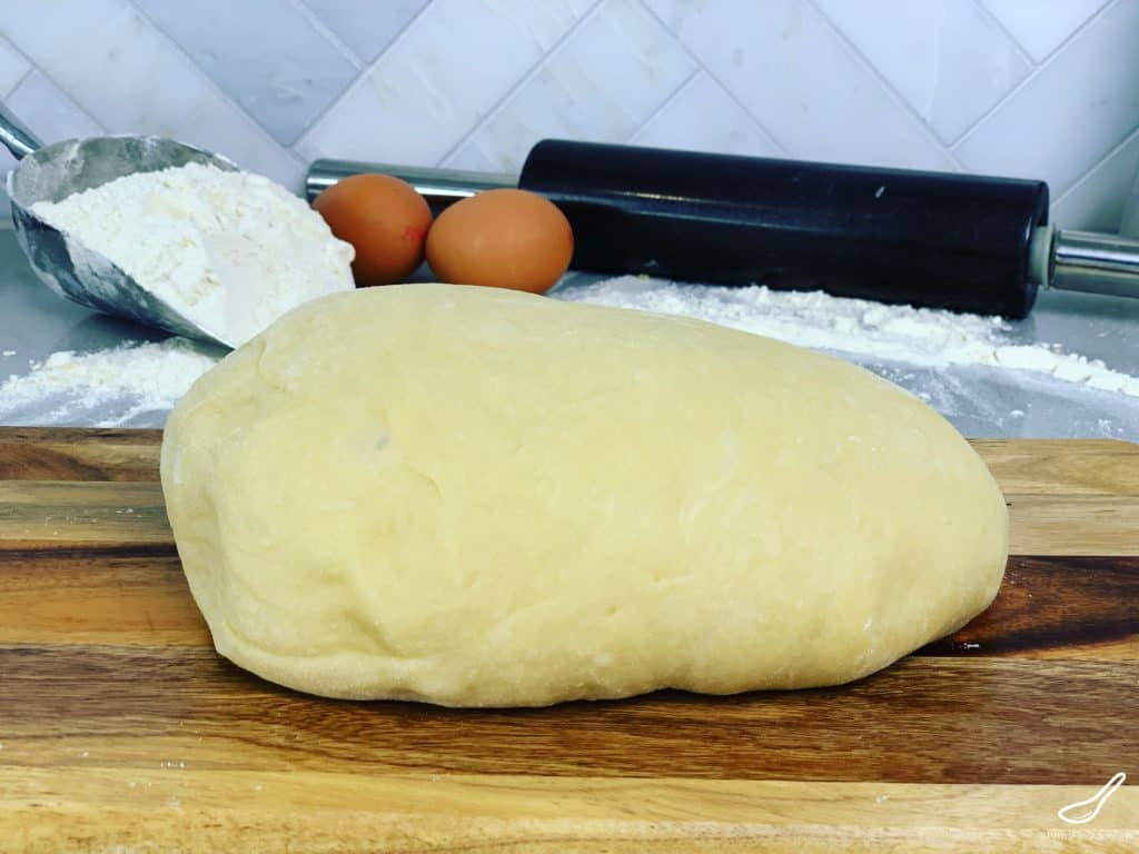 Yeast dough ball with rolling pin and flour