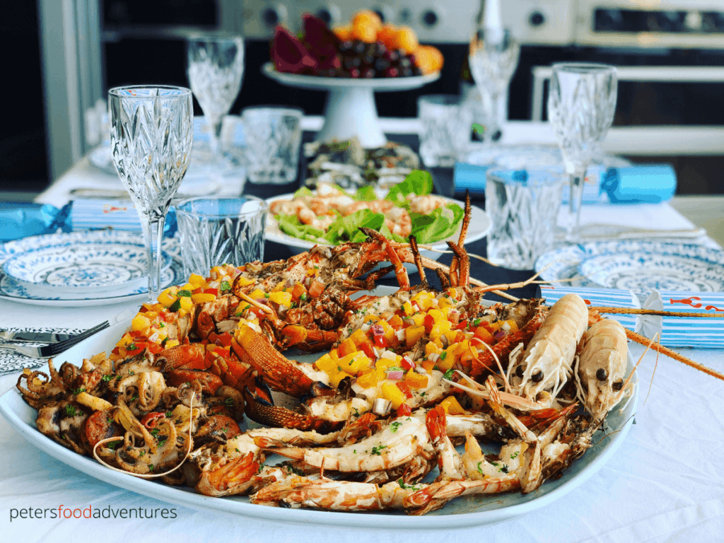 an aussie seafood feast on a platter, grilled lobsters, king prawns and octopus