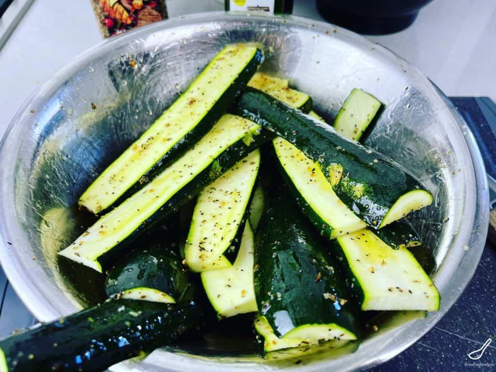 sliced zucchini marinating in a bowl