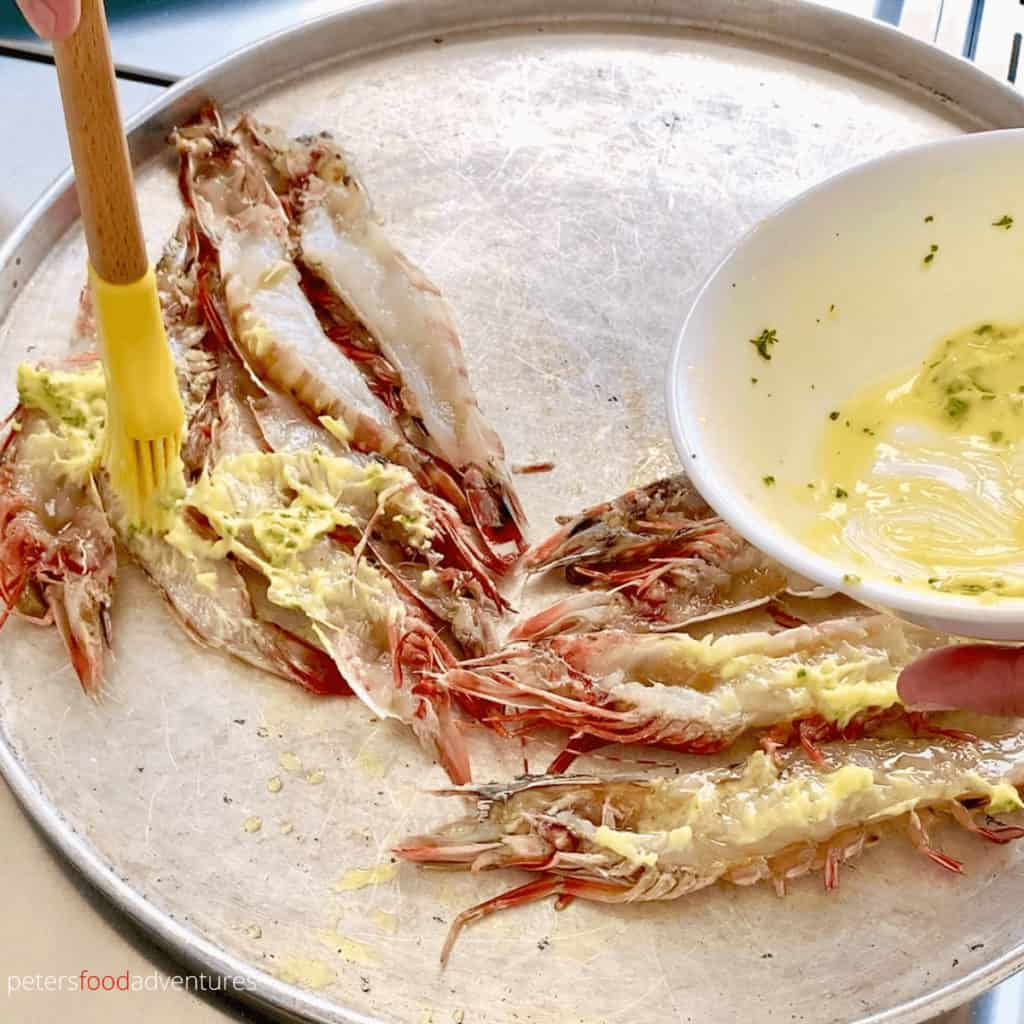 slathering garlic butter on jumbo prawns or king shrimp