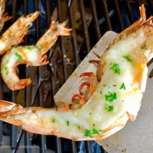Grilled King Prawns generously slathered in garlic butter, grilled to perfection! Butterflied Shrimp on the half shell is the perfect summer bbq feast!