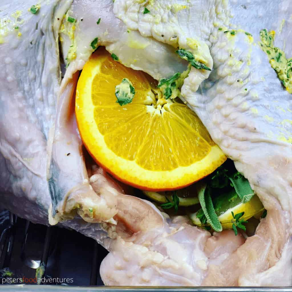 orange inside uncooked turkey cavity with herbs