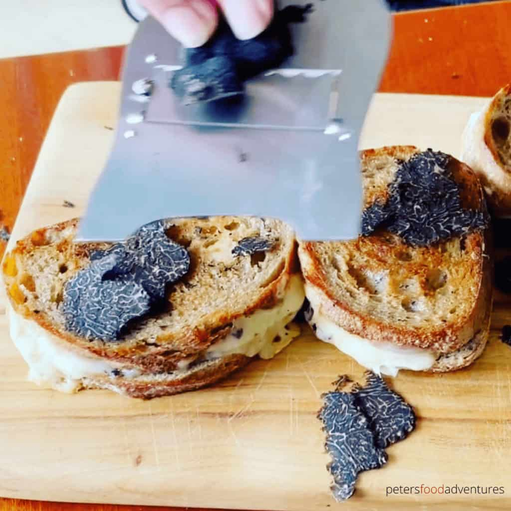 shaving truffles onto grilled cheese sandwich